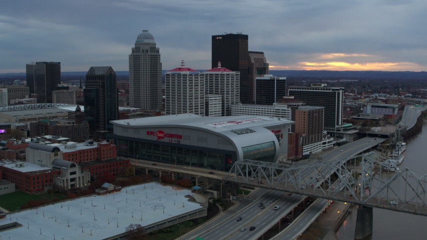 5.7K aerial video fly away from arena and skyline, reveal bridge and Ohio River at sunset, Downtown Louisville, Kentucky Aerial Stock Footage DX0001_003069