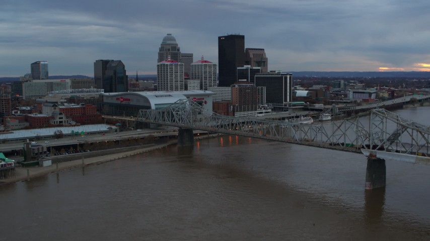 5.7K aerial video of the arena and skyline, seen while flying by bridge and Ohio River at sunset, Downtown Louisville, Kentucky Aerial Stock Footage DX0001_003070