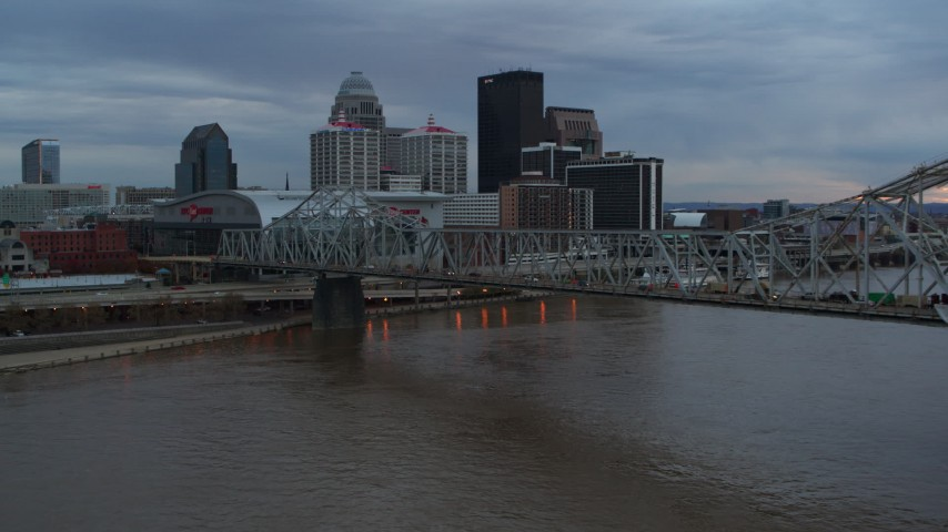 5.7K aerial video of flying by bridge and and ascend near the arena and city skyline at sunset, Downtown Louisville, Kentucky Aerial Stock Footage | DX0001_003071