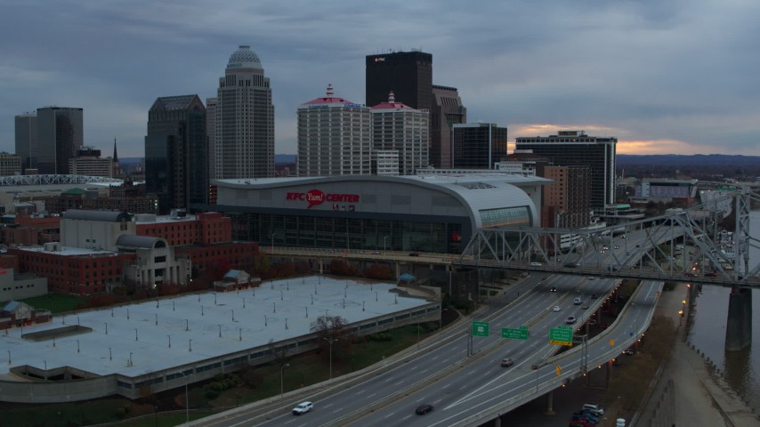 5.7K stock footage aerial video descend by freeway near the arena and city skyline at sunset, Downtown Louisville, Kentucky Aerial Stock Footage | DX0001_003072