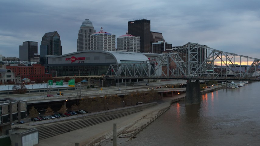 5.7K stock footage aerial video flyby freeway near the arena and city skyline, and bridge spanning river at sunset, Downtown Louisville, Kentucky Aerial Stock Footage DX0001_003073 | Axiom Images