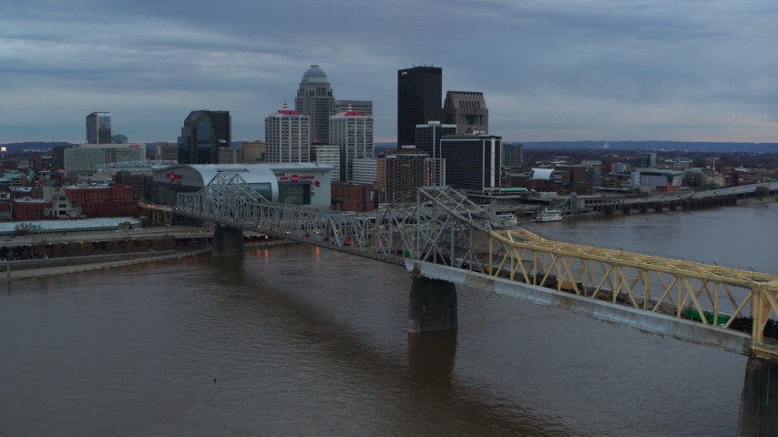 5.7K stock footage aerial video ascend by bridge spanning river at sunset for view of skyline, Downtown Louisville, Kentucky Aerial Stock Footage | DX0001_003074