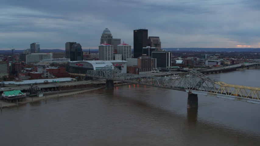 5.7K aerial video fly over the river to approach arena and city skyline at sunset, Downtown Louisville, Kentucky Aerial Stock Footage | DX0001_003076