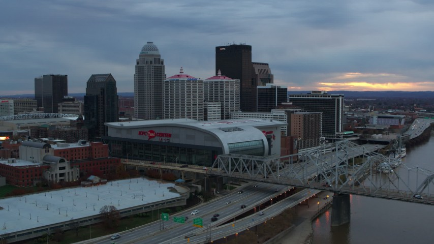 5.7K aerial video flyby river and bridge to pass arena and city skyline at sunset, Downtown Louisville, Kentucky Aerial Stock Footage | DX0001_003077
