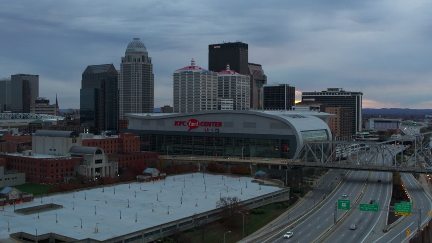 5.7K stock footage aerial video descend by freeway with view of arena and city skyline at sunset, Downtown Louisville, Kentucky Aerial Stock Footage DX0001_003078 | Axiom Images