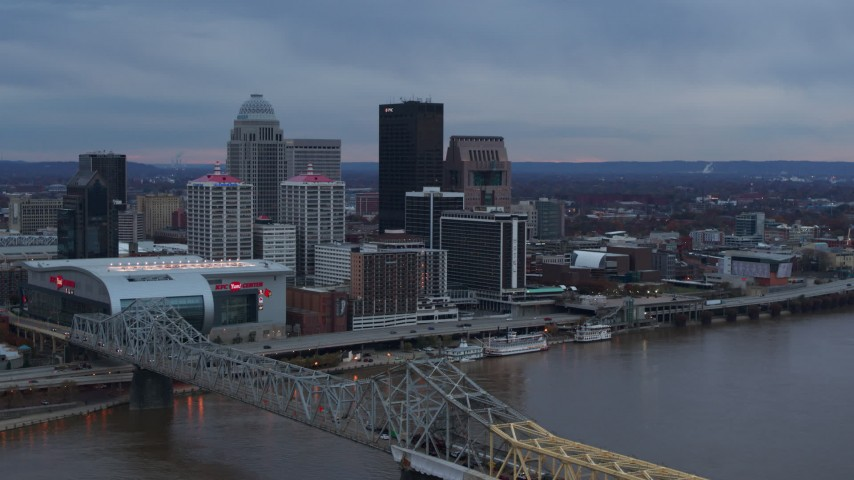 5.7K aerial video reverse view of city skyline at sunset while ascending by the bridge, Downtown Louisville, Kentucky Aerial Stock Footage | DX0001_003081