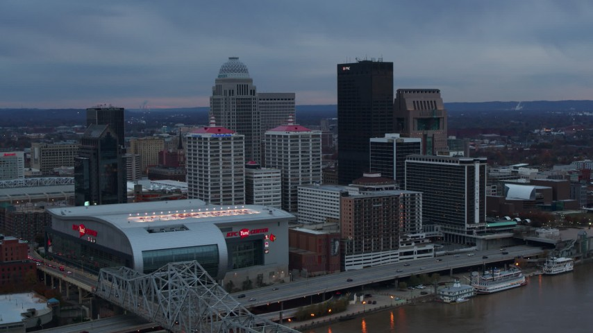 5.7K aerial video fly away from arena and city skyline at sunset, reveal river, Downtown Louisville, Kentucky Aerial Stock Footage | DX0001_003084