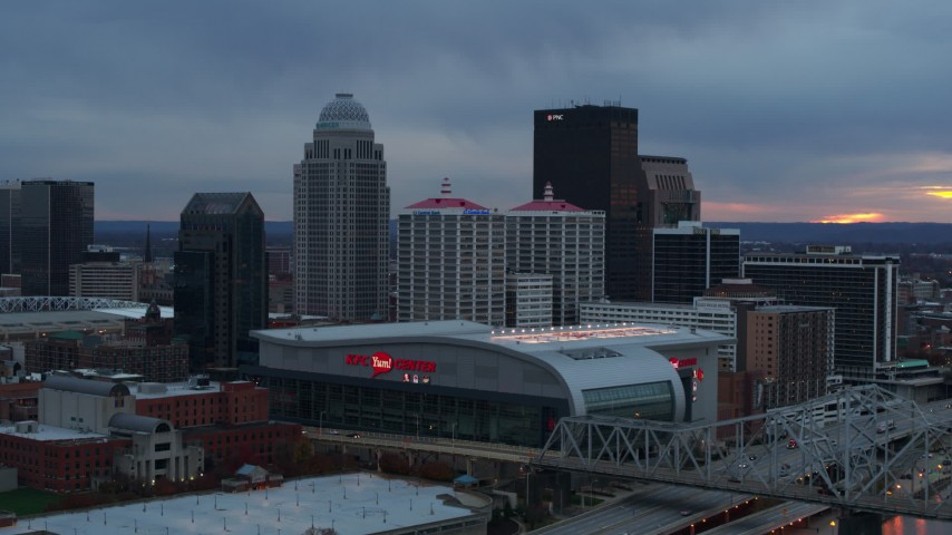 5.7K aerial video flyby arena and city skyline at sunset, seen while passing bridge, Downtown Louisville, Kentucky Aerial Stock Footage | DX0001_003086