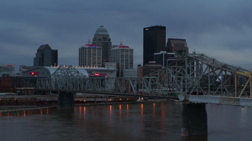 5.7K aerial video flyby bridge over the river at sunset toward arena, skyline in background, Downtown Louisville, Kentucky Aerial Stock Footage | DX0001_003090