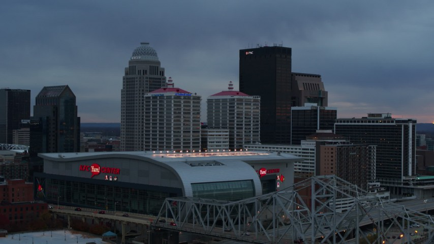 5.7K aerial video ascend by arena at sunset and focus on the skyline, Downtown Louisville, Kentucky Aerial Stock Footage | DX0001_003091