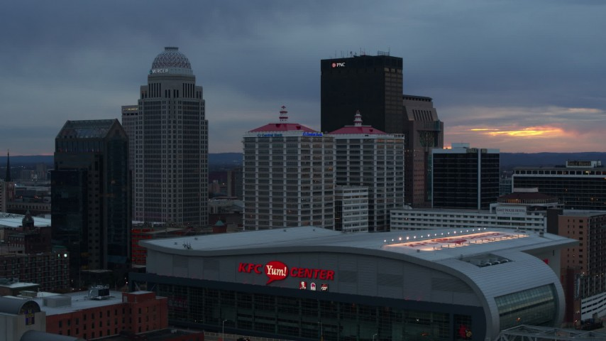 5.7K stock footage aerial video descend by arena at sunset and focus on the skyline, Downtown Louisville, Kentucky Aerial Stock Footage | DX0001_003092