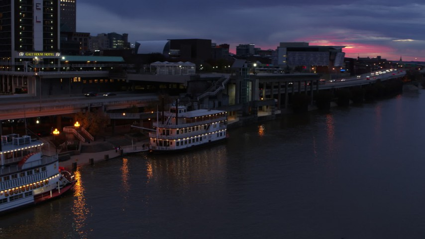 5.7K aerial video approach and orbit small riverboat at twilight in Downtown Louisville, Kentucky Aerial Stock Footage DX0001_003094