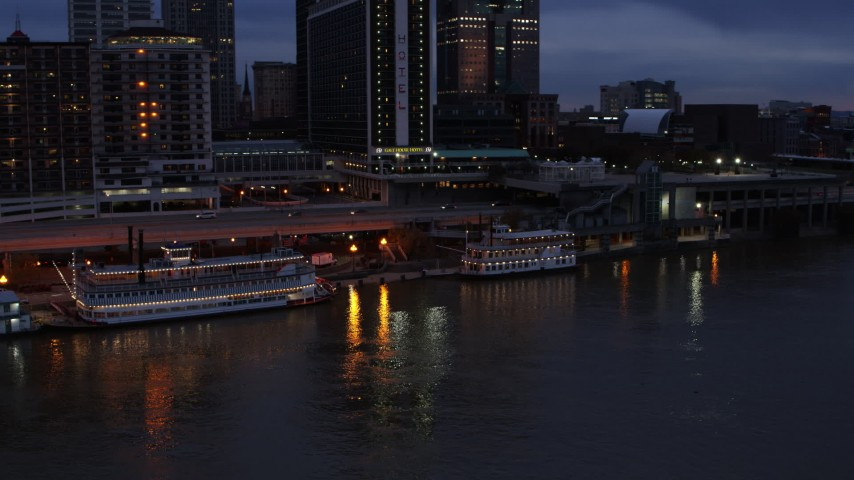 5.7K stock footage aerial video orbit small riverboat beside a historic ship at twilight in Downtown Louisville, Kentucky Aerial Stock Footage | DX0001_003095