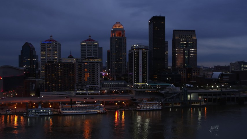 5.7K stock footage aerial video reverse view of the skyline at twilight, seen from Ohio River, Downtown Louisville, Kentucky Aerial Stock Footage | DX0001_003096
