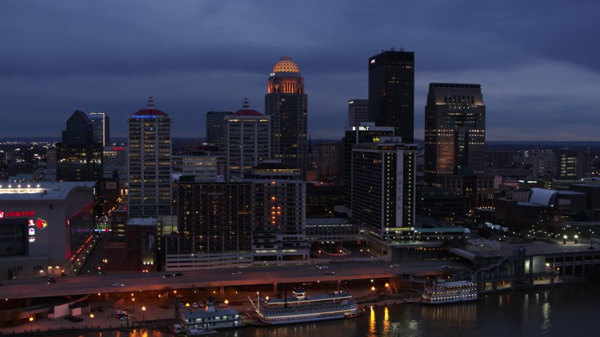 5.7K aerial video of flying by the skyline lit up at twilight, seen during ascent from Ohio River, Downtown Louisville, Kentucky Aerial Stock Footage | DX0001_003098