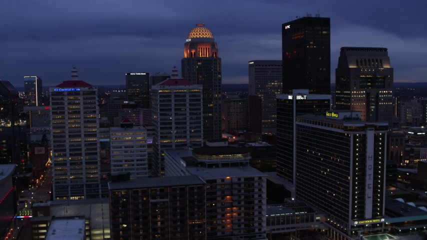 5.7K aerial video of flying by hotel, with the skyline lit up at twilight, Downtown Louisville, Kentucky Aerial Stock Footage | DX0001_003100