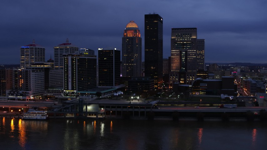 5.7K aerial video of reverse view of the skyline lit up at twilight, and the Ohio River, Downtown Louisville, Kentucky Aerial Stock Footage | DX0001_003101