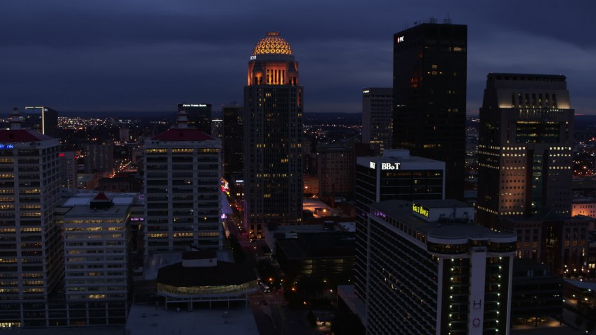 5.7K aerial video of a tall skyscraper lit up at twilight, Downtown Louisville, Kentucky Aerial Stock Footage | DX0001_003106