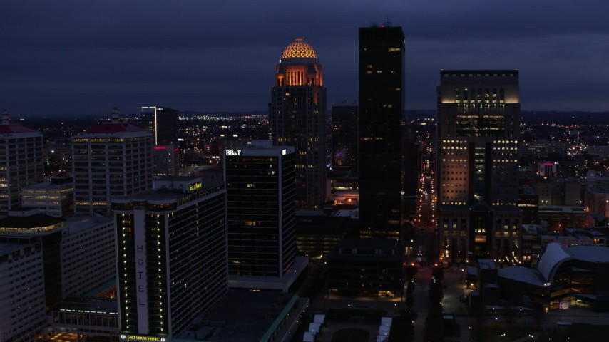 5.7K stock footage aerial video reverse view of a tall skyscraper and skyline lit up at twilight, Downtown Louisville, Kentucky Aerial Stock Footage | DX0001_003107