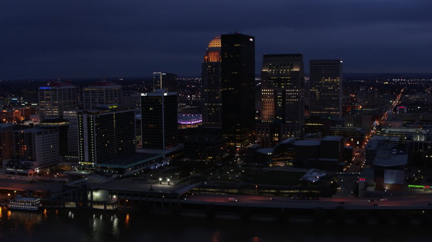 5.7K aerial video reverse view of the city's skyline at twilight, reveal Ohio River, Downtown Louisville, Kentucky Aerial Stock Footage DX0001_003108