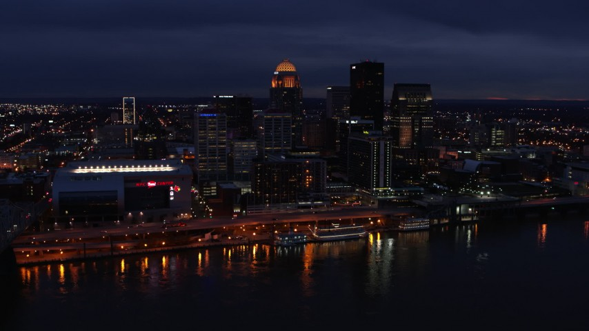 5.7K aerial video slowly fly away from and by the city's skyline at twilight, seen from Ohio River, Downtown Louisville, Kentucky Aerial Stock Footage | DX0001_003111