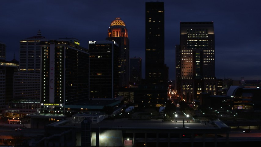 5.7K aerial video of flying by a hotel and skyscrapers at twilight, Downtown Louisville, Kentucky Aerial Stock Footage | DX0001_003114