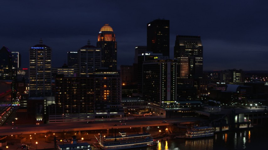 5.7K aerial video reverse view of hotel and the city skyline at twilight, reveal river, Downtown Louisville, Kentucky Aerial Stock Footage DX0001_003115