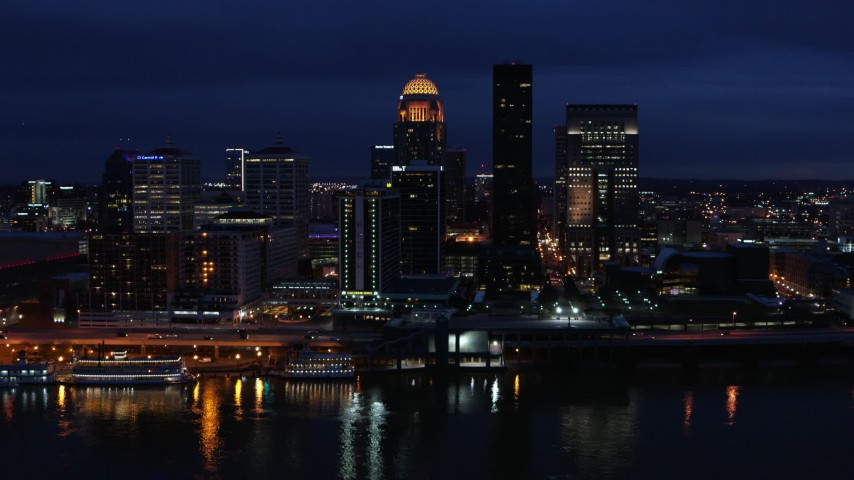 5.7K stock footage aerial video cross the Ohio River and ascend toward the city skyline at twilight, Downtown Louisville, Kentucky Aerial Stock Footage | DX0001_003117