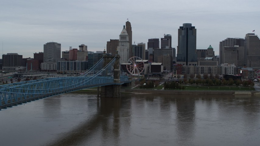 5.7K stock footage aerial video of the city skyline and Roebling Bridge seen from the Ohio River, Downtown Cincinnati, Ohio Aerial Stock Footage | DX0001_003133