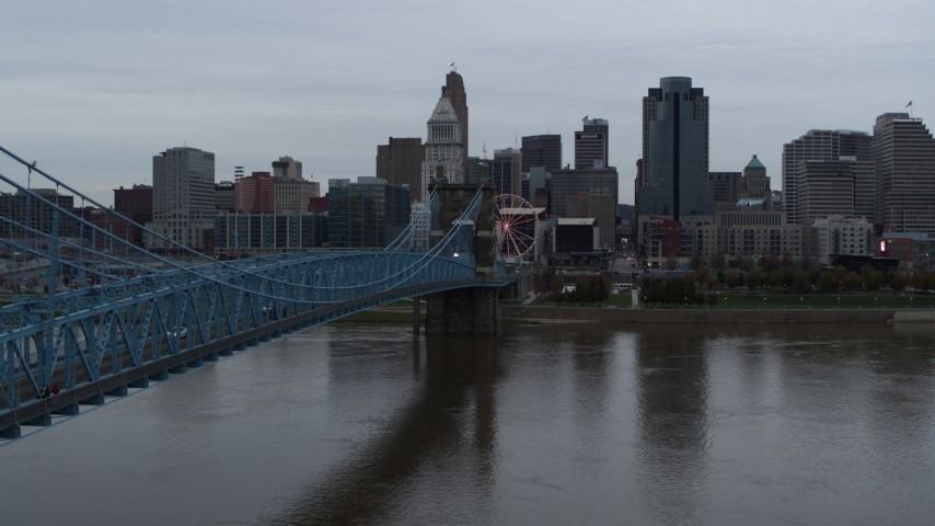 5.7K aerial video descend by bridge toward river, with view of the city skyline, Downtown Cincinnati, Ohio Aerial Stock Footage | DX0001_003136