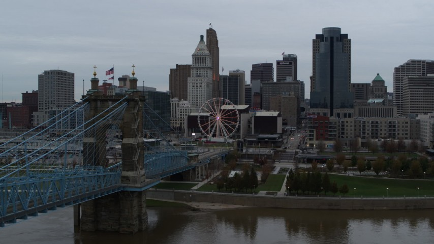 5.7K aerial video fly away from Ferris wheel and skyline, seen from bridge, and reveal river, Downtown Cincinnati, Ohio Aerial Stock Footage | DX0001_003142