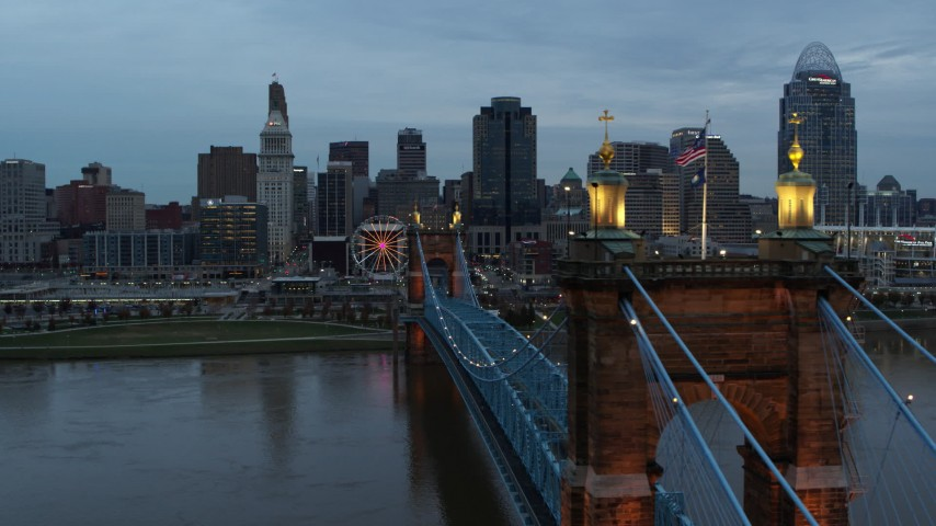 5.7K stock footage aerial video flyby the Roebling Bridge over the river at sunset, approach the skyline, Downtown Cincinnati, Ohio Aerial Stock Footage | DX0001_003154