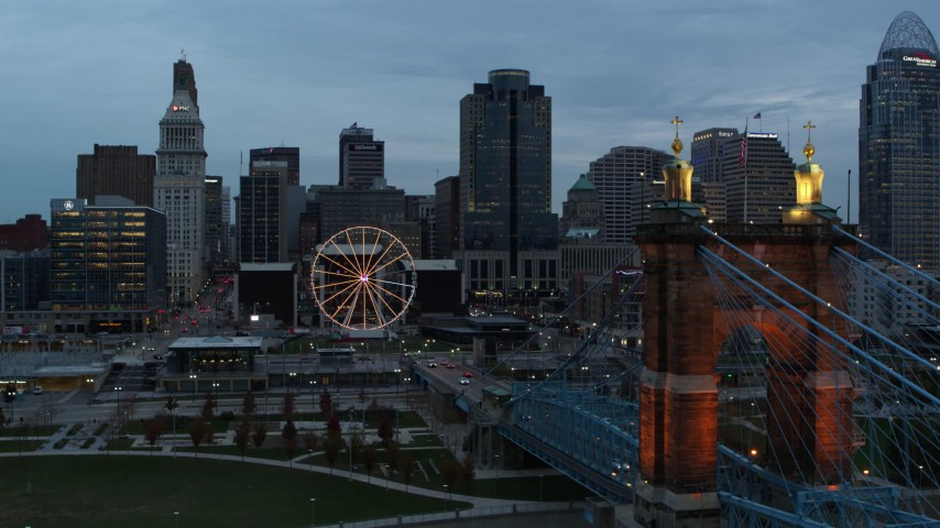 5.7K aerial video of Ferris wheel and city skyline at sunset during descent by bridge, Downtown Cincinnati, Ohio Aerial Stock Footage | DX0001_003156
