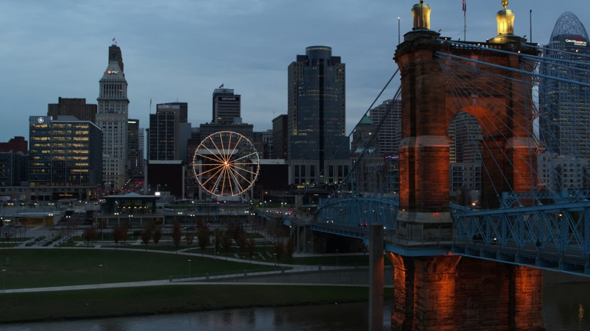 5.7K aerial video pass Roebling Bridge to approach Ferris wheel and city skyline at sunset, Downtown Cincinnati, Ohio Aerial Stock Footage | DX0001_003157