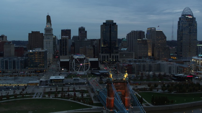5.7K aerial video ascend by Roebling Bridge for reverse view of Ferris wheel and city skyline at sunset, Downtown Cincinnati, Ohio Aerial Stock Footage | DX0001_003158