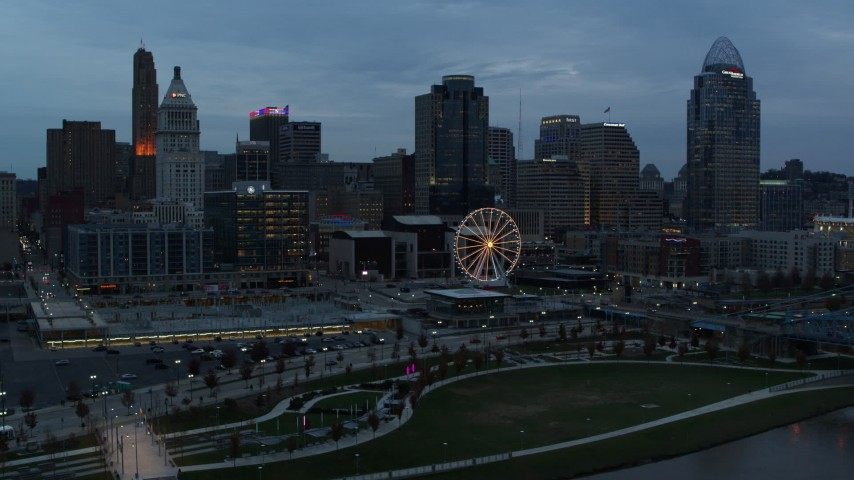 5.7K aerial video approach the city skyline and Ferris wheel at sunset from Ohio River, Downtown Cincinnati, Ohio Aerial Stock Footage | DX0001_003160