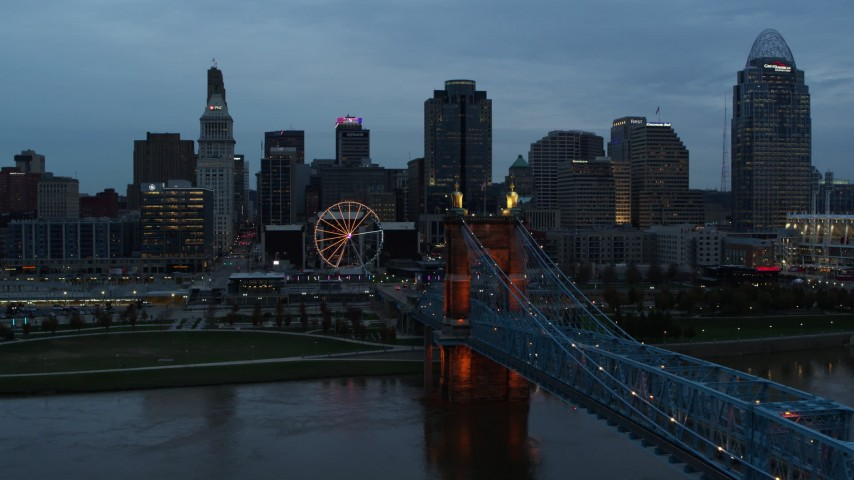 5.7K stock footage aerial video flyby city skyline and Ferris wheel at sunset, reveal bridge and Ohio River, Downtown Cincinnati, Ohio Aerial Stock Footage | DX0001_003161