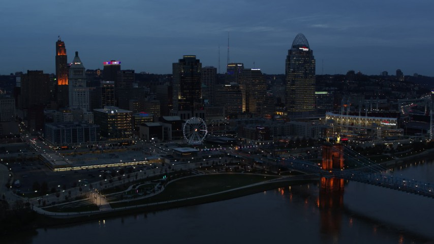 5.7K stock footage aerial video of the city skyline and bridge lit for twilight, seen from Ohio River, Downtown Cincinnati, Ohio Aerial Stock Footage | DX0001_003164