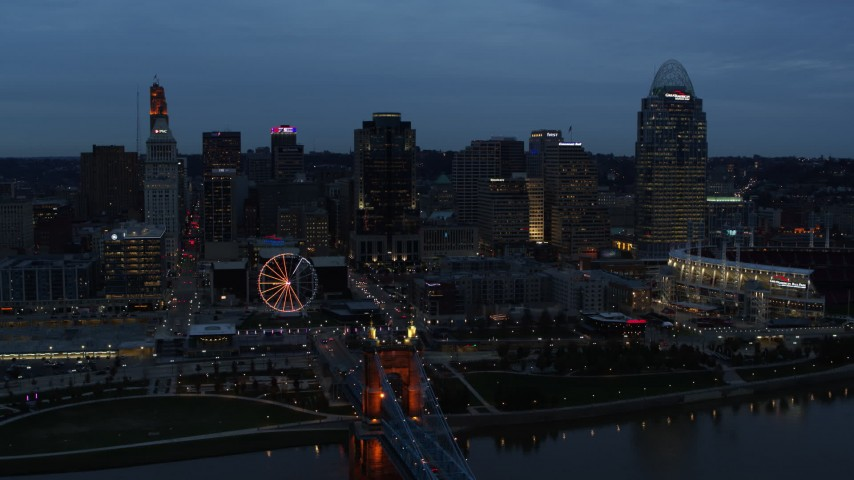 5.7K stock footage aerial video of the city skyline and bridge lit for twilight, and approach from Ohio River, Downtown Cincinnati, Ohio Aerial Stock Footage | DX0001_003165