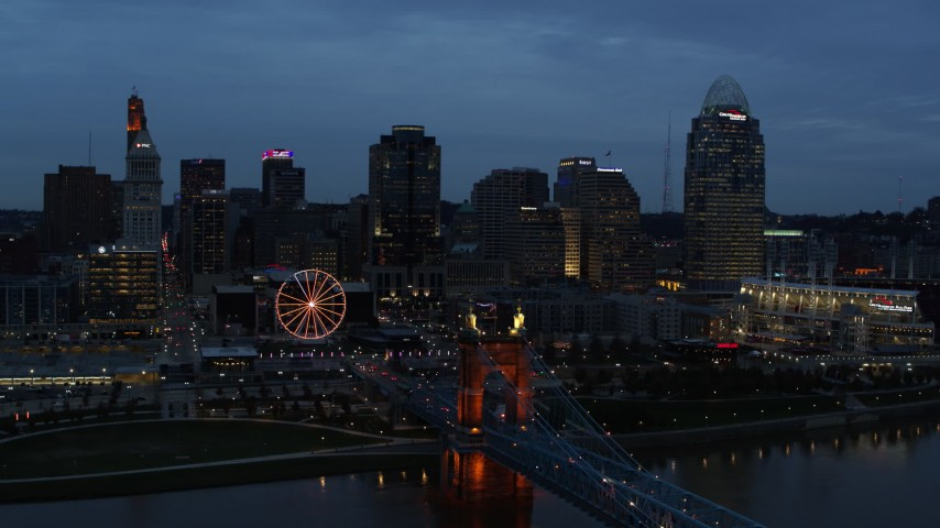5.7K aerial video flyby city skyline and bridge lit for twilight, seen from Ohio River, Downtown Cincinnati, Ohio Aerial Stock Footage | DX0001_003166