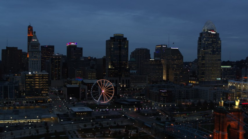 5.7K stock footage aerial video approach city skyline and Ferris wheel lit up at twilight, seen from Ohio River, Downtown Cincinnati, Ohio Aerial Stock Footage | DX0001_003167