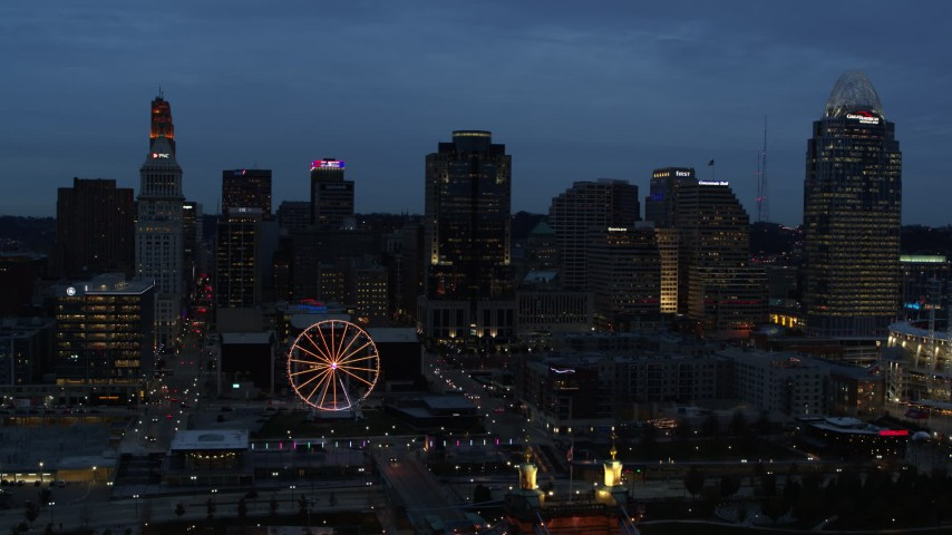 5.7K stock footage aerial video reverse view of city skyline and Ferris wheel lit up at twilight, reveal bridge and Ohio River, Downtown Cincinnati, Ohio Aerial Stock Footage | DX0001_003168