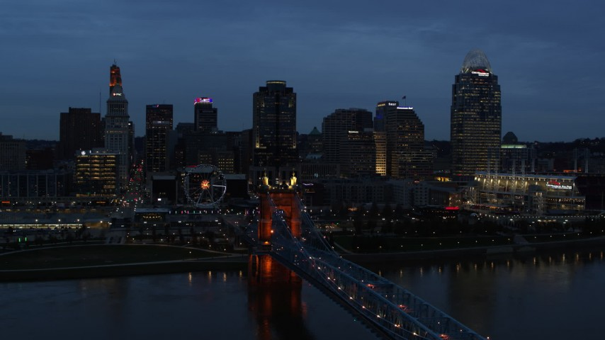 5.7K aerial video of city skyline and Roebling Bridge lit up at twilight, seen from Ohio River, Downtown Cincinnati, Ohio Aerial Stock Footage DX0001_003169