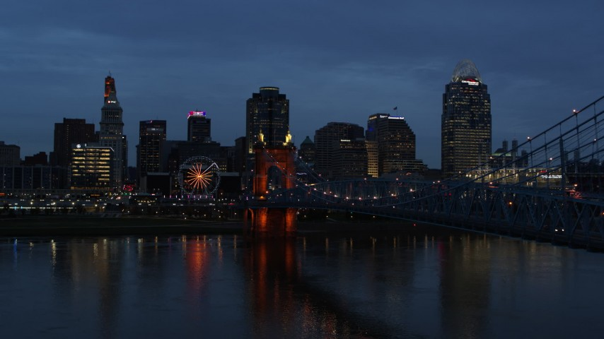 5.7K aerial video reverse view of city skyline and Roebling Bridge lit up at twilight, seen from Ohio River, Downtown Cincinnati, Ohio Aerial Stock Footage DX0001_003170