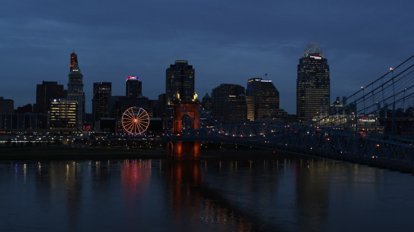 5.7K aerial video of city skyline behind Roebling Bridge lit up at twilight, seen from Ohio River, Downtown Cincinnati, Ohio Aerial Stock Footage DX0001_003171