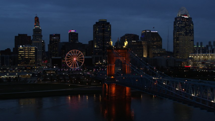 5.7K aerial video flyby Roebling Bridge lit up at twilight, and away from city skyline, Downtown Cincinnati, Ohio Aerial Stock Footage | DX0001_003174