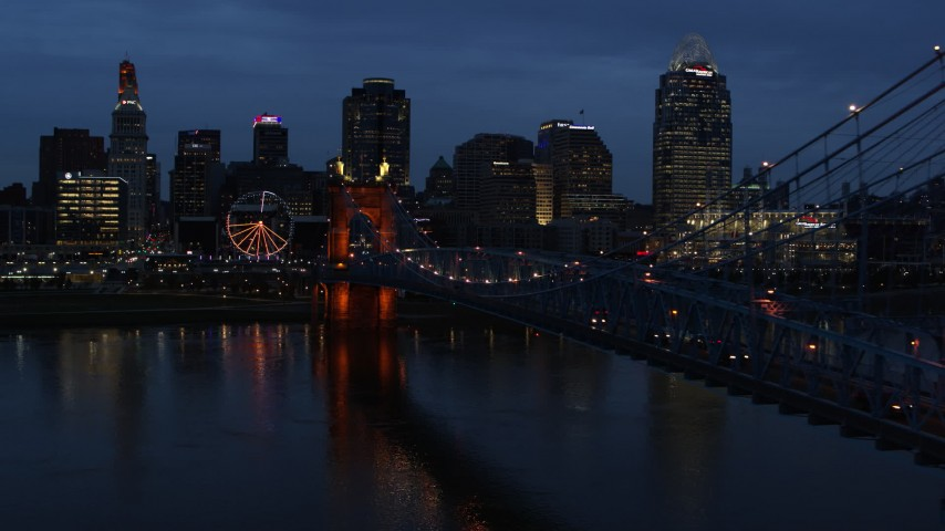 5.7K aerial video follow Roebling Bridge lit up at twilight, approach city skyline, Downtown Cincinnati, Ohio Aerial Stock Footage | DX0001_003175