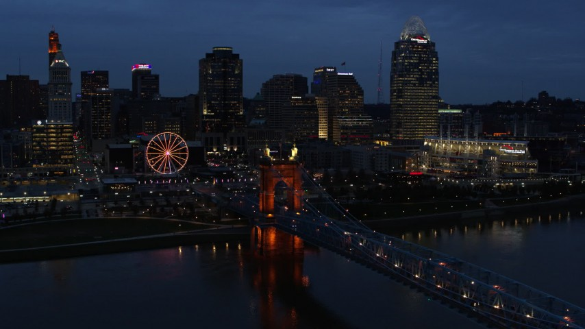 5.7K stock footage aerial video fly away from city skyline lit up at twilight, reveal the bridge and river, Downtown Cincinnati, Ohio Aerial Stock Footage | DX0001_003177