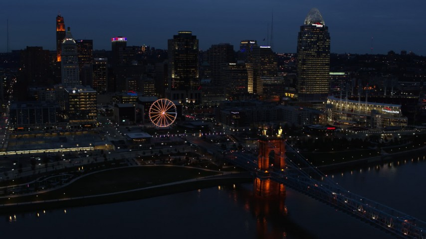 5.7K aerial video flying by lights of city skyline and bridge at twilight, seen from river, Downtown Cincinnati, Ohio Aerial Stock Footage | DX0001_003178