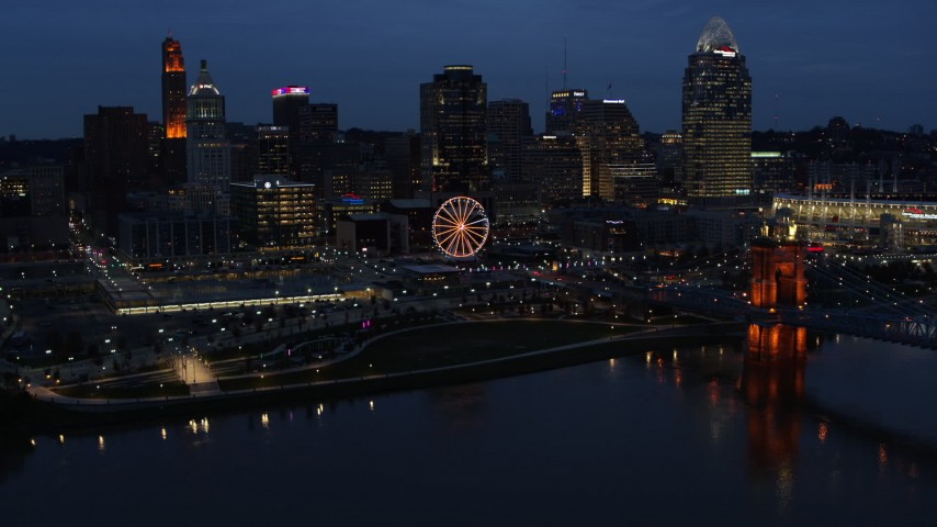 5.7K stock footage aerial video flying by lights of city skyline and bridge at twilight, seen from across river, Downtown Cincinnati, Ohio Aerial Stock Footage | DX0001_003179